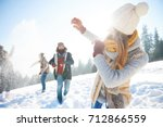 young couple in snowball fight  | Shutterstock . vector #712866559