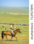 Small photo of Ulaanbaatar, Mongolia - June 12, 2007: Panning shot of Mongolian man in tradtional garb riding horse across the steppe in the grassy countryside