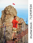 Small photo of Man is walking along a suspension bridge over an abyss. Yalta, the Crimea. The concept of risk and danger.