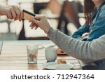 cropped shot of couple paying... | Shutterstock . vector #712947364