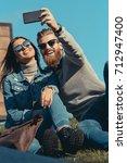 happy couple taking selfie... | Shutterstock . vector #712947400