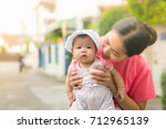 the mother is carrying  the... | Shutterstock . vector #712965139