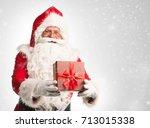 santa claus holding a present ... | Shutterstock . vector #713015338