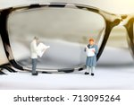 Small photo of Miniature people reading and standing on book with glasses using as background, education or business concept.