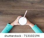 kid holding glass of milk on... | Shutterstock . vector #713102194