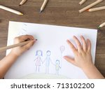 Small photo of Child drawing happy family on paper. Top View