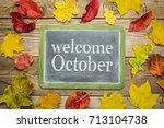 Small photo of Welcome October on a slate blackboard against rustic weathered wood planks with colorful dried leaves