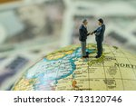 Small photo of Miniature figure men handshaking standing on north korea and japan map globe as peace and war agreement negotiation concept.