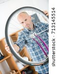 Small photo of Man aligning bicycle wheel