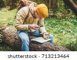male traveler sat down on a log ...   Shutterstock . vector #713213464
