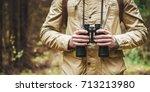 man with binoculars standing in ... | Shutterstock . vector #713213980