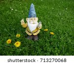 Small photo of Garden dwarf with mobile phone on a green meadow makes a selfi with peace sign