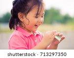 little asian girl smiling with... | Shutterstock . vector #713297350
