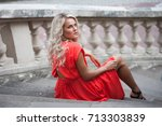 woman in a red dress poses on... | Shutterstock . vector #713303839
