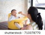 mom is feeding baby food.   Shutterstock . vector #713378770