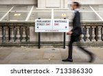 Small photo of LONDON, UK - 29 AUGUST 2017: Whitehall civil servant. Anonymous blur of a suited office worker passing a street sign for Parliament Street and Whitehall in the civil service district of Westminster.