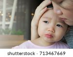 mother soothing crying little... | Shutterstock . vector #713467669