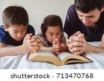 parent and children praying on... | Shutterstock . vector #713470768