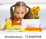 little girl is having breakfast ... | Shutterstock . vector #713483938