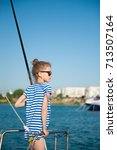 Small photo of young little girl in sunglasses sunbathing aboard recreational boat