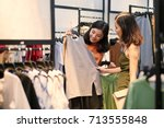 Small photo of Fashion consultant showing clothes to the client