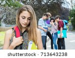 unhappy girl being gossiped... | Shutterstock . vector #713643238