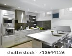 Stock photo interiors shots of a modern kitchen whose floor is made of hardwood in the foreground the kitchen 713644126