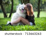 Stock photo pretty girl hugging and kissing her dog at the park outdoor samoyed 713663263