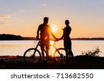 Couple On A Bicycle At Sunset...