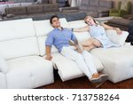 Small photo of Young couple admire new sofa-transformer in the store.