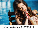 girl with a cocktail sits by... | Shutterstock . vector #713775919