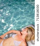 Small photo of Woman on air mattress in pool