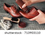 worker holding brown shoe and... | Shutterstock . vector #713903110