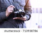photographer holding vintage... | Shutterstock . vector #713938786