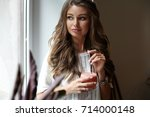 attractive young woman drinking ... | Shutterstock . vector #714000148
