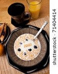 The word FOOD spelled out of letter shaped cereal pieces floating in a milk filled cereal bowl. Surrounding is an orange juice coffee and toast with jelly. - stock photo