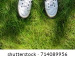 white sneakers on a green grass ... | Shutterstock . vector #714089956