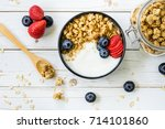 bowl of granola with yogurt ... | Shutterstock . vector #714101860