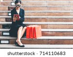 woman sitting near red shopping ... | Shutterstock . vector #714110683