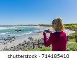 woman on ocean rocks   west... | Shutterstock . vector #714185410