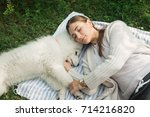 young woman resting with a dog... | Shutterstock . vector #714216820