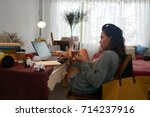 Stock photo college student drinking coffee and working on laptop in her room 714237916