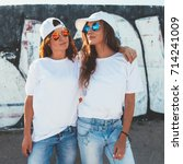Small photo of Two models wearing plain white t-shirts and hipster sunglasses posing against street wall. Teen urban clothing style, same look. Mockup for tshirt print store.