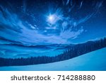 Stock photo majestic winter night in a mountain valley with full moon in a starry sky 714288880