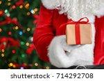 Santa Claus Holding Gift Box...