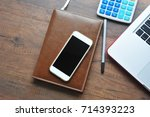 smartphone on wood work space. | Shutterstock . vector #714393223