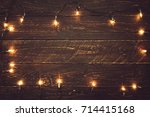 christmas lights bulb on wood... | Shutterstock . vector #714415168