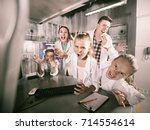 Small photo of Cheerful positive family of five is depisting madness in time having fun together in lost labroom.