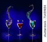 three glasses with colored liquid splashing on a deep blue background - stock photo