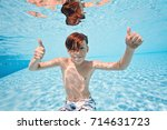 happy young boy swim and dive... | Shutterstock . vector #714631723